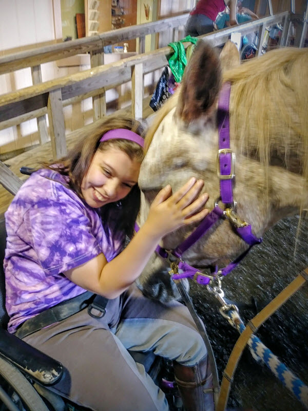 Image of individual hugging a horse